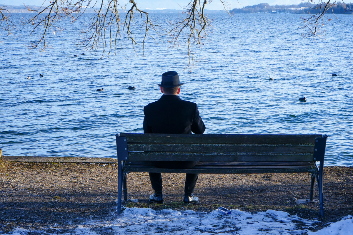 By the roadside # 1285 Tutzing, February 14, 2021: A man dressed in black sits on a bench on the shore of Lake Starnberg in Tutzing on a cool winter afternoon.
